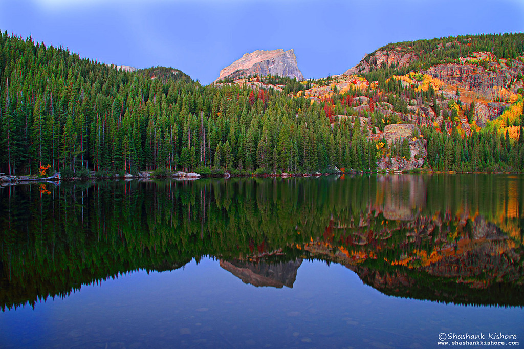 Location - Bear lake, RMNP CO, USA Shot 10 min before Sunrise. Great reflection can be captured during sunrise or sunset.  (Second week of Sept 2010) Canon 7D, 17-85@17mm, f9, ISO-160, 4 Sec.  I was lucky enough to capture the reflection. I was able to take just 4-5 shots and wind started blowing which ruined the reflection. I recommend arriving 30 min before Sunrise or Sunset at the spot which i could not do. If you get plenty of time, you can set multiple exposures and take shots in different compositions.